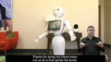 Pepper, a humanoid robot with a screen on her chest, interacts with her friend.